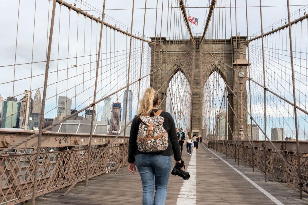 femme avec sac à dos et appareil photo sur brooklyn bridge